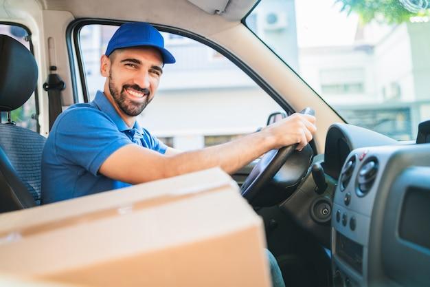 Retrato de um motorista de entregador dirigindo van com caixas de papelão no assento. serviço de entrega e conceito de transporte.
