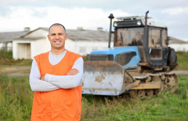 Retrato de um motorista de escavadeira contra fazenda