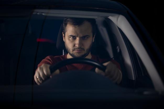 Retrato de um motorista sério, confiante e com barba por fazer, sentado ao volante do carro à noite, olhando para o futuro