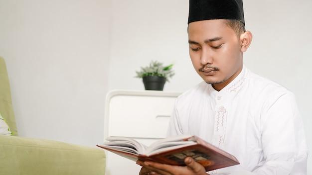 Retrato de um muçulmano asiático lendo o alcorão sagrado em casa