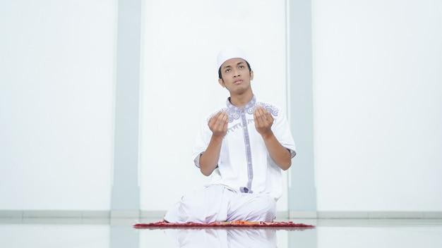 Retrato de um muçulmano asiático rezando na mesquita após o shalat