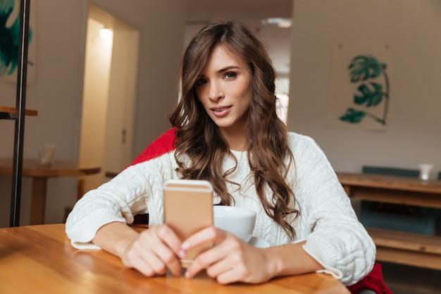 Retrato, de, um, mulher bonita, segurando telefone móvel