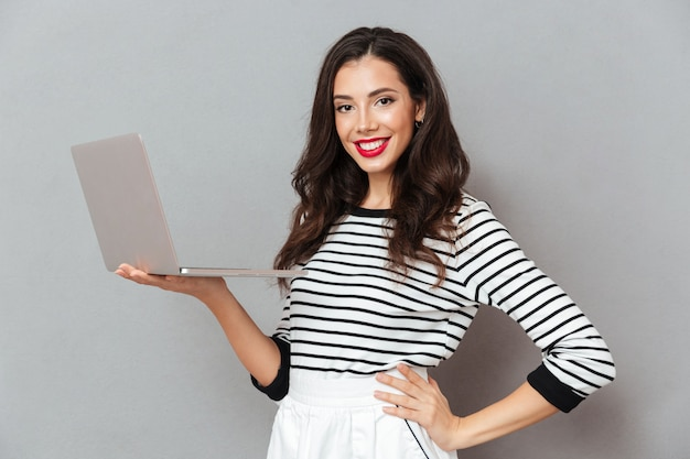 Retrato, de, um, mulher confiante, segurando computador portátil