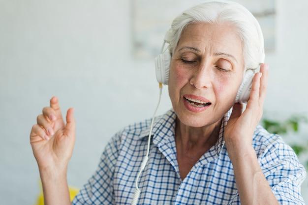 Retrato, de, um, mulher idosa, desfrutando, a, música, ligado, headphone