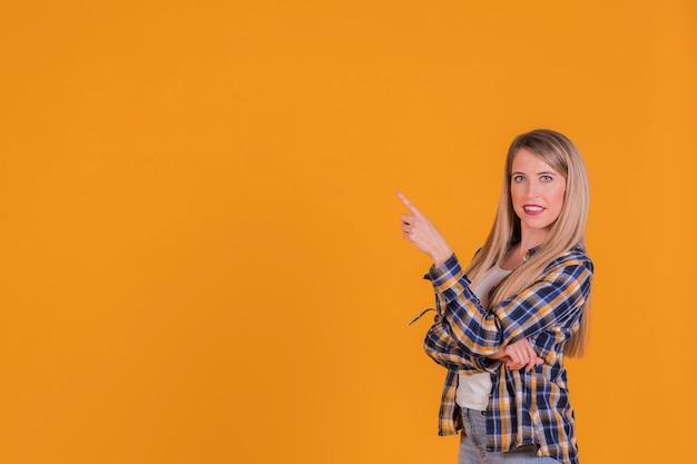 Retrato, de, um, mulher jovem, apontar, seu, dedo, contra, um, laranja, fundo