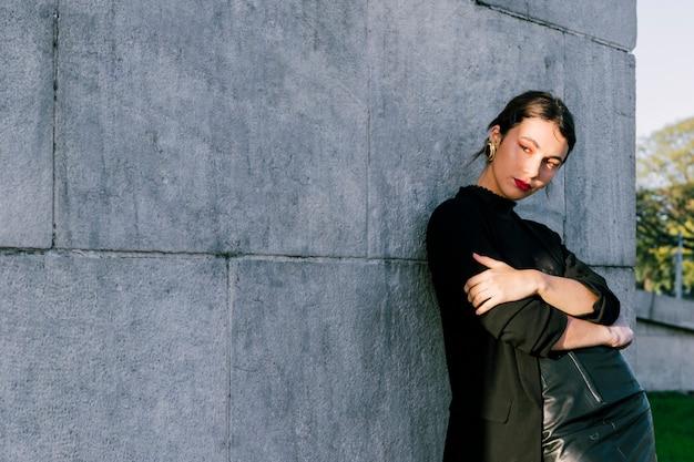 Retrato, de, um, mulher jovem, com, dela, braços cruzaram, ficar, contra, parede