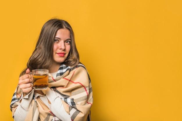 Retrato, de, um, mulher jovem, embrulhado, em, xale, segurando, xícara chá herbal