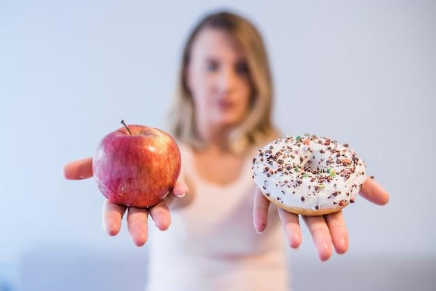 Retrato, de, um, mulher jovem, escolher, entre, donut, e, maçã vermelha