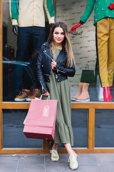 Retrato, de, um, mulher jovem, posar, frente, janela, exposição, segurando, bolsas para compras, em, mão