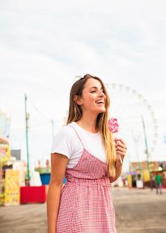 Retrato, de, um, mulher jovem, segurando, grande, pirulito, em, parque divertimento