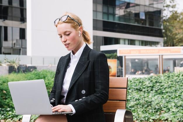 Retrato, de, um, mulher jovem, sentando, exterior, a, escritório, usando computador portátil