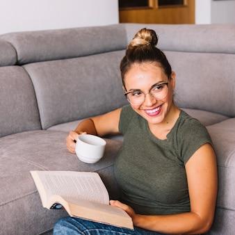 Retrato, de, um, mulher jovem, sentar sofá, segurando, xícara café, e, livro, em, mãos