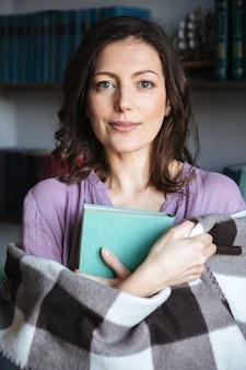 Retrato, de, um, mulher madura, coberto cobertor, segurando livro
