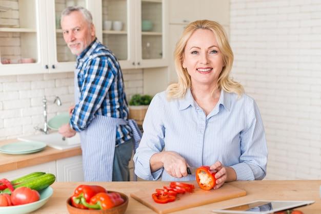 Retrato, de, um, mulher sênior, corte, a, pimentão, com, faca, e, seu, marido, lavando pratos, em, pia cozinha