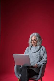 Retrato, de, um, mulher sênior, sentando, ligado, poltrona, usando, a, laptop, contra, fundo vermelho
