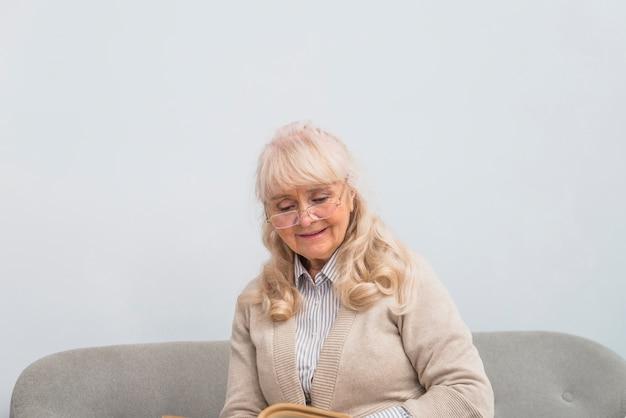 Retrato, de, um, mulher sênior, sentando, ligado, sofá, livro leitura
