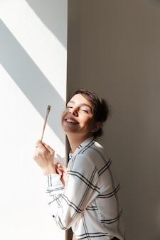 Retrato, de, um, mulher sorridente, artista, segurando, painbrush, e, posar