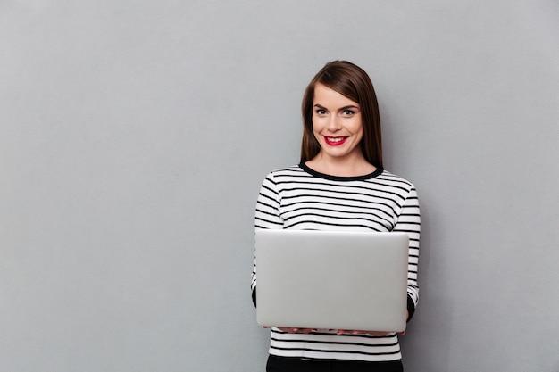 Retrato, de, um, mulher sorridente, segurando computador portátil