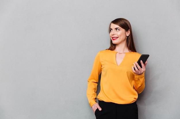 Retrato, de, um, mulher sorridente, segurando telefone móvel