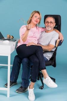 Retrato, de, um, mulher sorridente, sentando, ligado, colo, enquanto, sentar-se cadeira