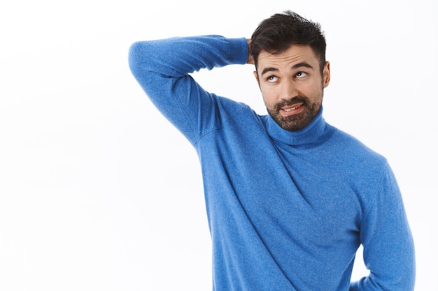 Retrato de um namorado barbudo atraente, indeciso e sem noção de gola olímpica, coçar a cabeça e olhando para cima, evitando contato visual, confessando que esqueceu de fazer a tarefa, parado em uma parede branca sem noção