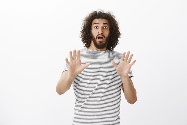 Retrato de um namorado hispânico atraente assustado e chocado com cabelo e barba afro, levantando as mãos em defesa e gritando de surpresa, curvando-se para trás