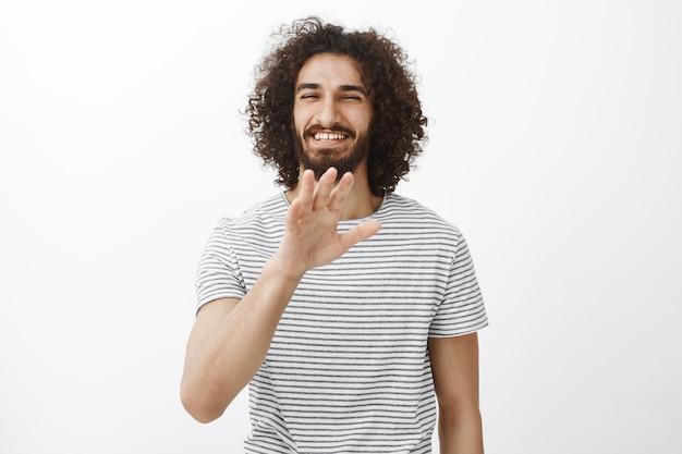 Retrato de um namorado hispânico encantador e despreocupado com cabelo encaracolado e barba, acenando com a palma da mão em nenhum agradecimento ou gesto de parar e sorrindo amplamente com atitude amigável