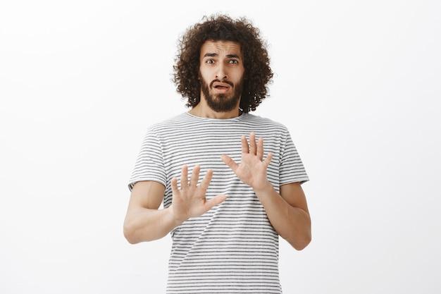 Retrato de um namorado hispânico fofo envergonhado com barba, sendo surpreendido com uma oferta inesperada, levantando as mãos em gesto de não ou rejeição, tentando negar ou recusar algo
