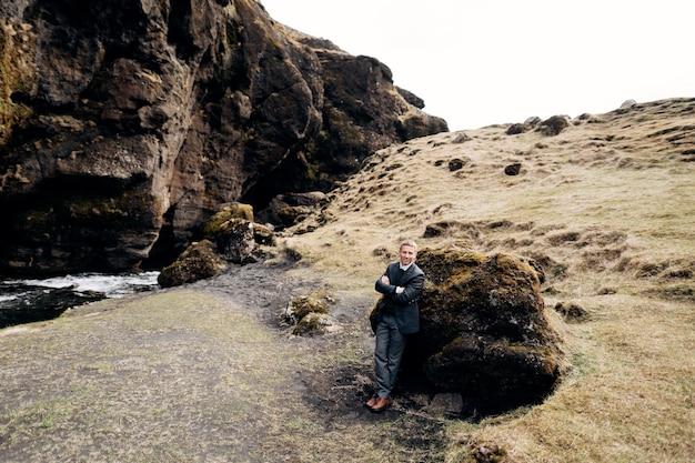 Retrato de um noivo apoiado em uma pedra em um musgo próximo a uma fenda rochosa com um rio na montanha