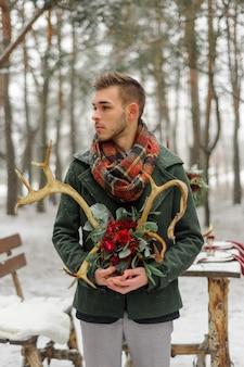 Retrato de um noivo barbudo em um elegante terno com suspensórios e gravata borboleta no inverno em uma estação de esqui