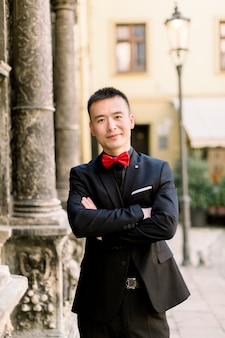 Retrato de um noivo chinês jovem bonito de terno preto e gravata vermelha com os braços cruzados, ao estar ao ar livre na cidade velha.