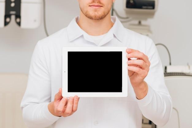 Retrato de um optometrista masculino apresentando modelo de tablet