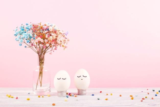 Retrato de um ovo da páscoa com as flores na mesa rosa.