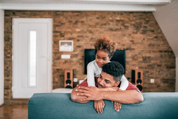 Retrato de um pai afro-americano e de uma filha loving em casa.