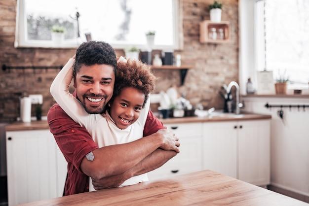 Retrato de um pai afro-americano feliz e de uma filha em casa.