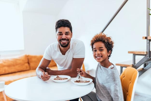 Retrato de um pai afro-americano feliz e de uma filha que comem o café da manhã.