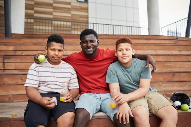 Retrato de um pai afro-americano positivo, sentado no banco da arquibancada de madeira e abraçando os filhos em uma partida esportiva