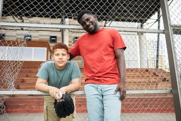 Retrato de um pai afro-americano sorridente com barba abraçando um filho adolescente com uma bola e uma luva de beisebol