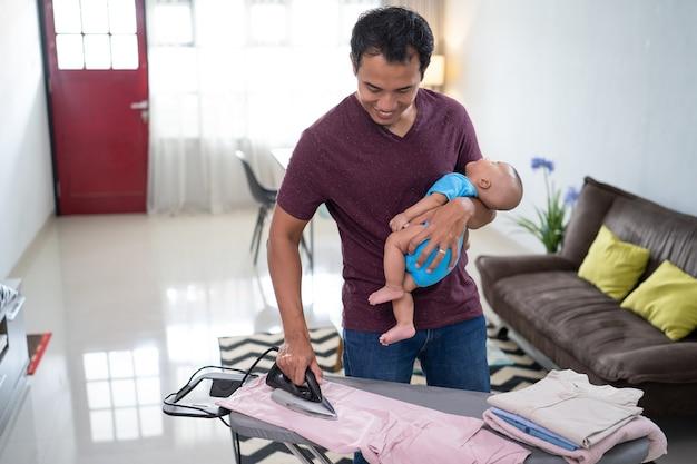 Retrato de um pai asiático passando suas roupas enquanto segura seu bebê nas mãos