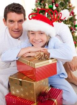 Retrato de um pai e seu filho segurando presentes de natal