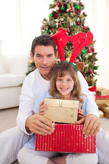 Retrato de um pai e sua filha segurando presentes de natal