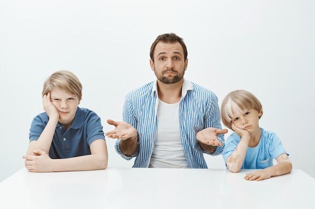 Retrato de um pai europeu bonito e questionado sentado à mesa com filhos entediados e chateados, dando de ombros com as palmas das mãos levantadas, sem ter a menor ideia de como criar meninos sozinho