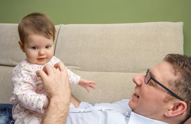 Retrato de um pai feliz brincando com um bebê fofo sentado sobre a barriga em um sofá em casa