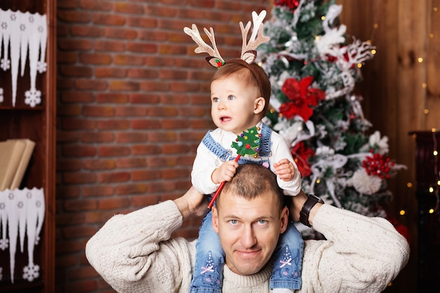 Retrato de um pai feliz e sua adorável filha entre as decorações de natal
