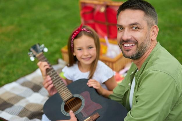 Retrato de um pai feliz sorrindo para a câmera enquanto está sentado com sua linda filha na grama verde em