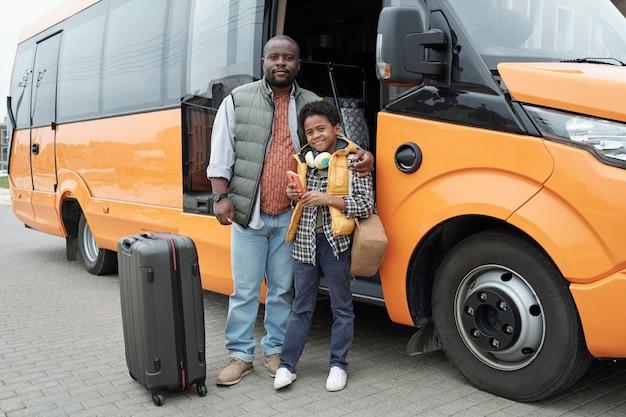 Retrato de um pai negro careca abraçando o filho contra a porta aberta de um ônibus moderno, viajando de ônibus