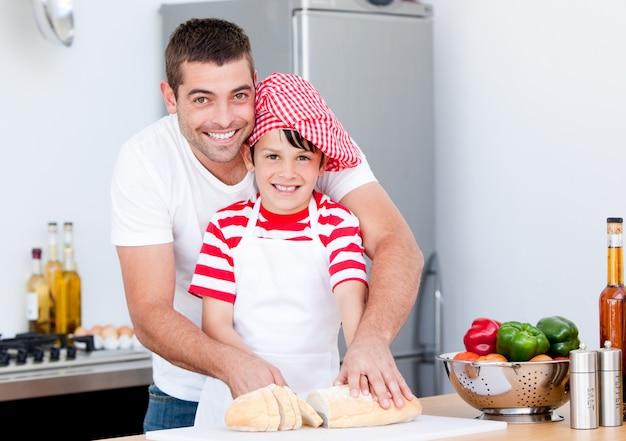 Retrato de um pai sorridente e seu filho preparando uma refeição