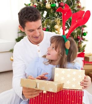 Retrato de um pai sorridente e sua filha abrindo presentes de natal