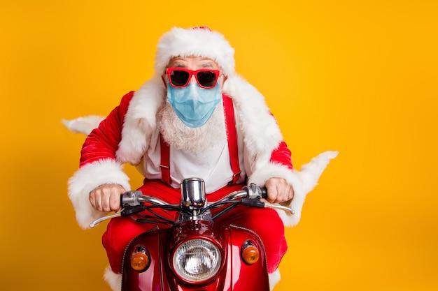 Retrato de um papai noel idoso, moderno e descolado, de cabelos grisalhos, usando máscara de segurança de gaze, dirigindo uma motocicleta, entregando presentes, venda de casa isolada sobre fundo de cor amarelo brilhante