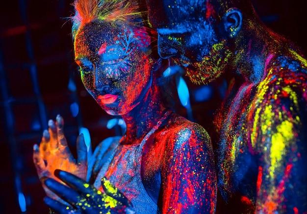 Retrato de um par de amantes pintados em pó fluorescente.